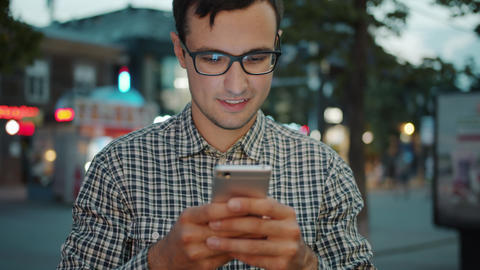 Portrait of attractive man in glasses using smartphone touching screen outdoors Footage