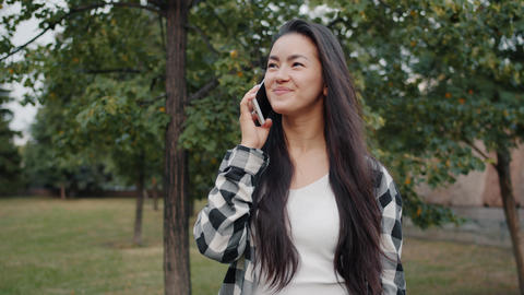 Cheerful Asian lady chatting on cellphone in green park in summer outdoors Footage