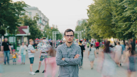 Time lapse of young serious businessman in glasses outdoors in urban street Footage