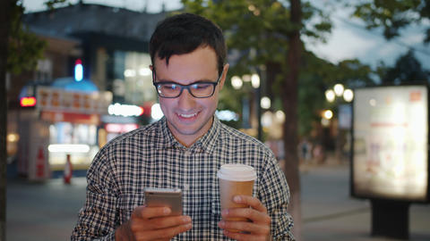 Cheerful businessman using smartphone holding to go coffee in street in evening Footage
