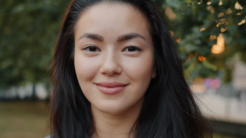 Slow motion of attractive Asian lady smiling outside in park on summer day Footage