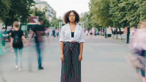 Zoom in time lapse of serious Afro-American woman in glasses outdoors in city Footage