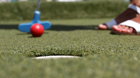 Minigolf, miniature golf or Mini Putt - woman putting with club ball in hole Live Action