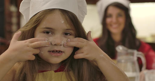 Close-up face of cheerful little Caucasian girl drawing lines on face with flour Live Action