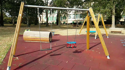 empty swings with chains swaying at playground for child, moved from wind, slow Live Action