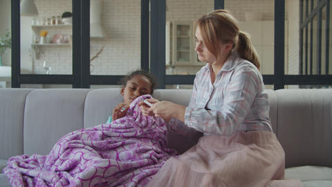 Caring mother comforting her sick daughter at home Live Action