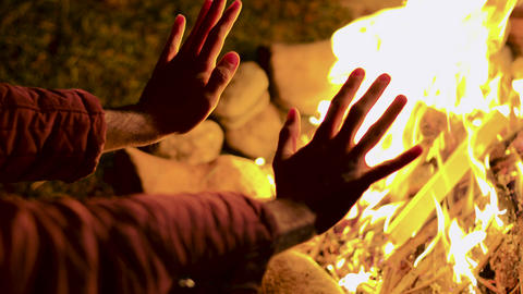 Young man warming up his hand at camp fire in a cold night of autumn Live Action