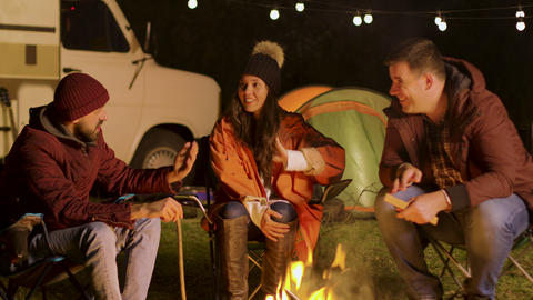 Group of close friend relaxing together around camp fire in a cold night of Footage