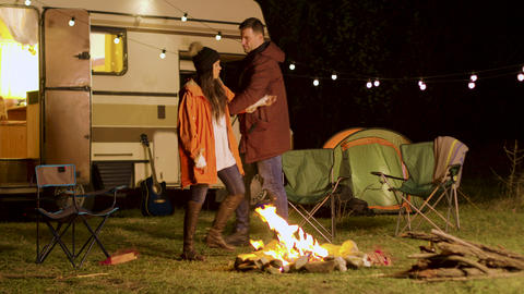 Cheerful young couple dancing around camp fire in cold night of autumn Live Action