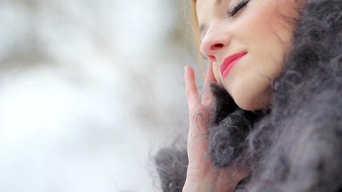 Beautiful girl in a down scarf under a winter snowfall in the forest Archivo