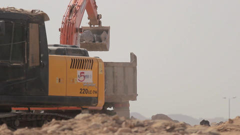 Excavator scoop loads a dump truck Footage