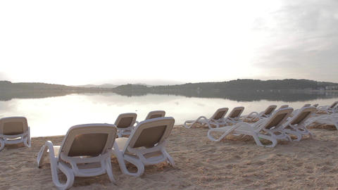 Sunrise at the beach - there are sunbed - wide angle pan Footage