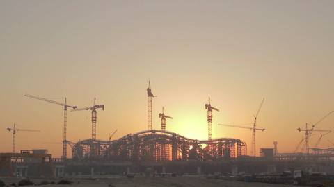 Sunrising appears from behind a silhouette building of the construction site - T Footage