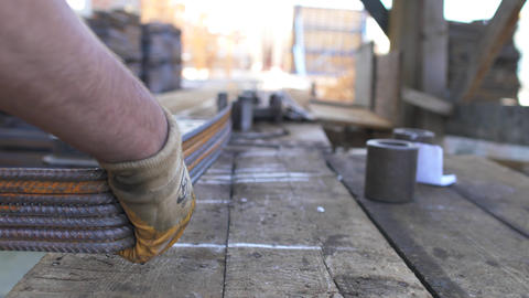 Worker is twisting steel pipe construction materials in a construction site Live Action