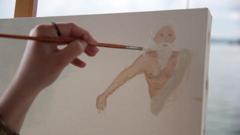Woman artist painting with paintbrush next to sea - close up Footage
