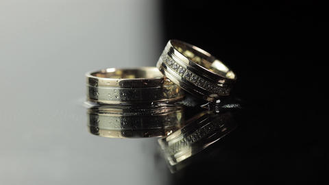 Wedding rings on black and white water surface shining with light. Close up Live Action