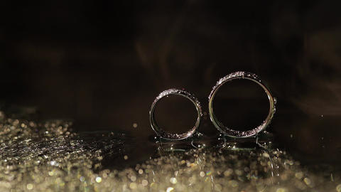 Wedding rings on dark water surface shining with light. Water drops. Close up Live Action