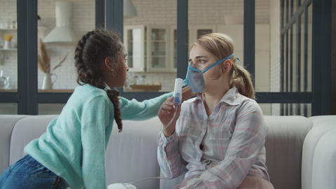Cute daughter consoling ill mom in nebulizer mask Live Action