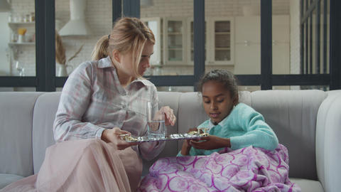 Caring mother giving pills and water to sick kid Live Action
