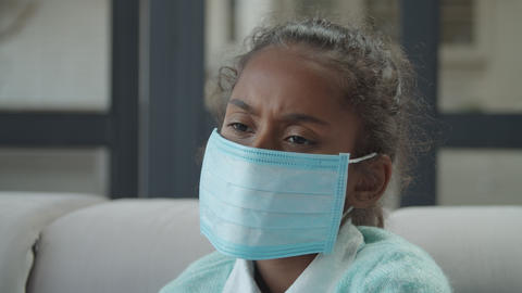 Sad sick girl wearing medical mask indoors Footage