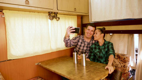 Beautiful young couple making a selfie inside of their retro camper van Footage
