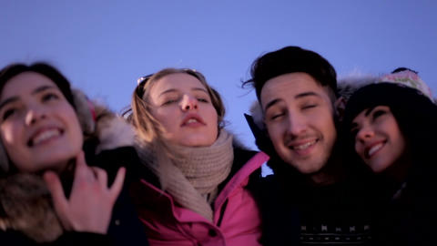 Three funny girls and a guy on a background of blue sky on a sunny winter day Live Action