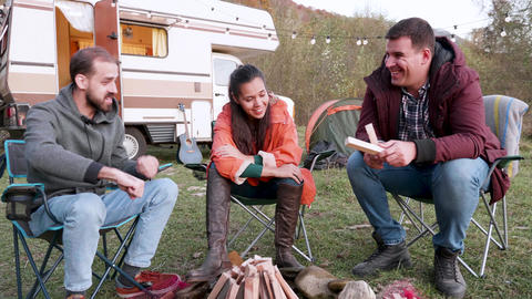 Caucasian friends relaxing together in front of their camper van Footage