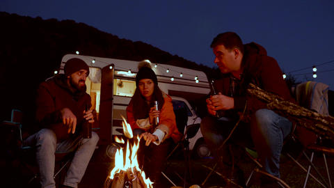 Caucasian friend enjoying a beer together in front of their retro camper Footage