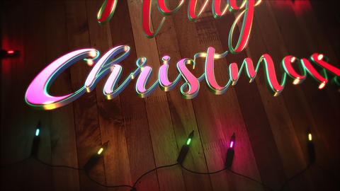 Animated closeup Merry Christmas text and colorful garland on wood background Videos animados