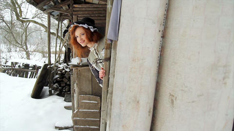 Red-haired girl in ethnic clothes in the yard of a old rustic house Live Action