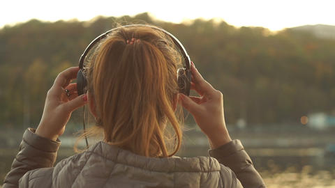 Relaxed Red-haired Girl puts on headphones and enjoys music on the background of Footage