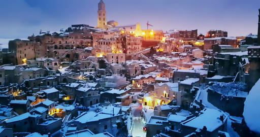 panoramic view of typical stones Sassi di Matera and church of Matera under blue night sky, time ビデオ
