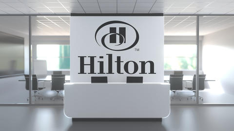 Logo of HILTON on a wall in the modern office, editorial conceptual 3D animation Live Action
