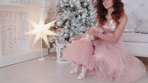 Beautiful mother with a one-year-old daughter in beautiful dresses and New Year Footage