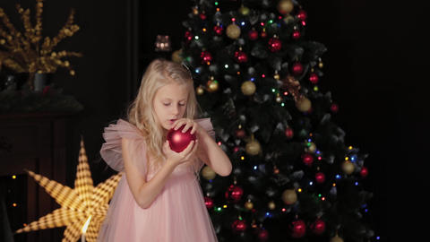 A ten-year-old girl near the New Year tree holds a New Year s toy in her hands Live Action