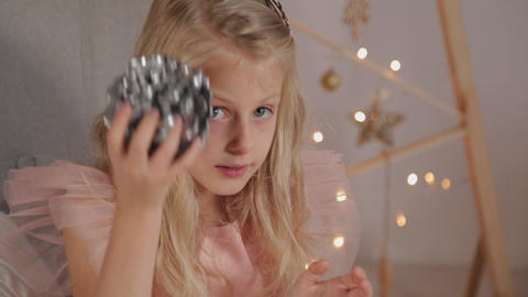 A nine-year-old girl in New Year s decor holds a New Year s toy in her hands Live Action