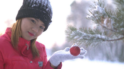 Asian Girl decorating Christmas tree in forest Footage