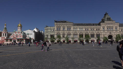 Asian, Caucasian tourists walk and make photos on Red Square, pan right Footage
