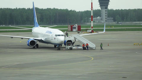 Passengers go inside airliner, parked at empty apron field. Time lapse shot Footage