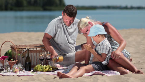 Beautiful family picnicking on the beach Filmmaterial