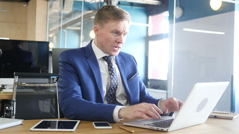 Unhappy businessman with computer getting bad news in office Live Action