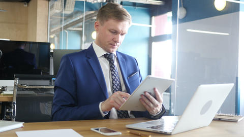 Young businessman typing email on tablet computer in office Footage