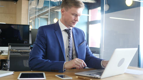 Businessman starting his working day, sitting at the desk with laptop Footage