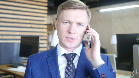 Seroius angry young businessman talking on a smartphone Footage