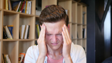 Feeling awful headache. Depressed young man touching his head with hands Live Action