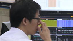 CHINESE STOCK MARKET TRADER WORRYING WHILE LOOKING AT SHARE PRICES Footage
