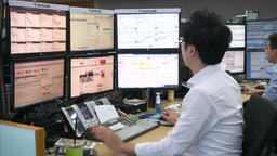 TRADER STOCKBROKER DEALER TYPING AND LOOKING AT MONITORS KOREA STOCK EXCHANGE Footage