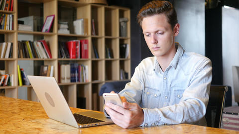 Happy attractive young man sitting and using smartphone in office Footage