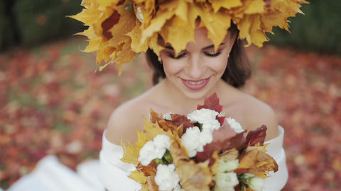 Happy bride in autumn park. Woman wearing wreath of yeloow leafs. The bride Live Action