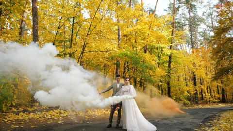 Slow motion. Young attractive Bride and Groom hold burning smoke bombs and walk Footage